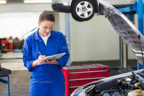 Mechanic examining under hood of carの写真素材 [FYI00005046]
