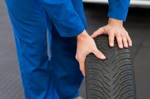 Mechanic rolling a tire wheelの素材 [FYI00005048]