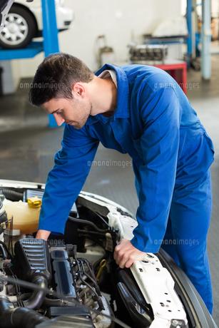 Mechanic examining under hood of carの写真素材 [FYI00005051]