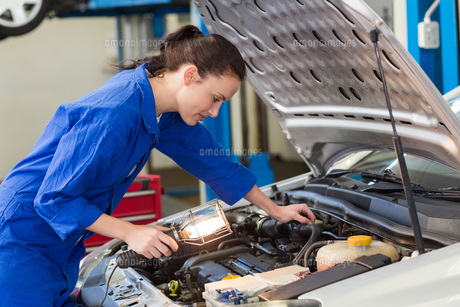 Mechanic examining under hood of car with torchの写真素材 [FYI00005053]