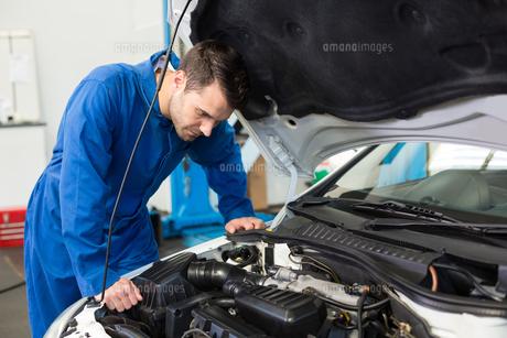 Mechanic examining under hood of carの写真素材 [FYI00005054]