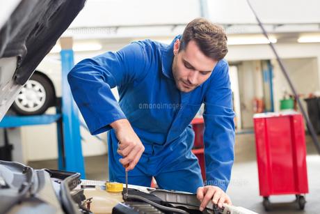 Mechanic examining under hood of carの写真素材 [FYI00005056]