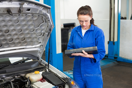 Mechanic examining under hood of carの写真素材 [FYI00005062]