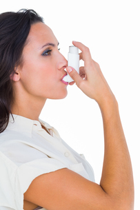 Asthmatic brunette using her inhalerの写真素材 [FYI00005099]