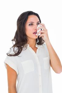 Asthmatic brunette using her inhalerの写真素材 [FYI00005100]