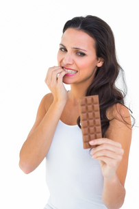 Pretty brunette fearfully looking at chocolateの写真素材 [FYI00005105]