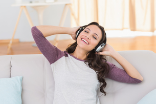 Pretty brunette listening to music on the couchの写真素材 [FYI00005116]