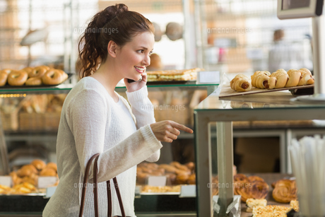 Pretty brunette picking out a pastryの写真素材 [FYI00005126]