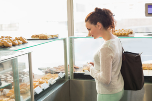 Pretty brunette picking out a pastryの写真素材 [FYI00005128]