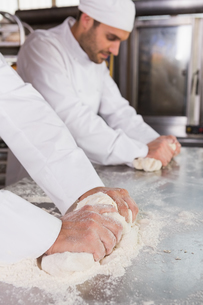 Focused bakers kneading dough at counterの写真素材 [FYI00005149]