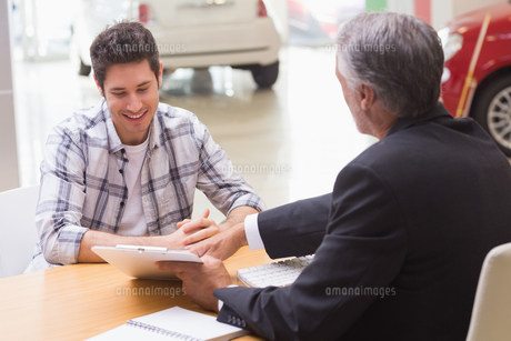 Salesman showing client where to sign the dealの素材 [FYI00005154]