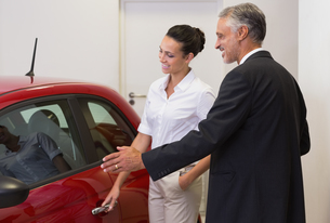 Businessman showing a car to a womanの写真素材 [FYI00005159]