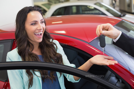 Excited woman receiving car keyの写真素材 [FYI00005163]