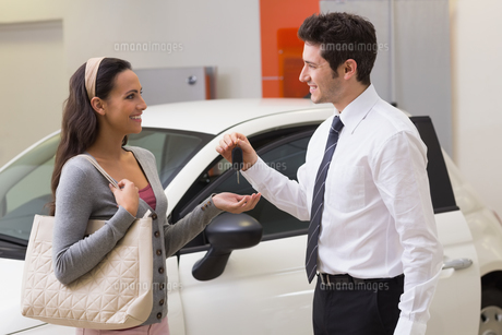 Smiling businessman giving car key to happy customerの写真素材 [FYI00005165]