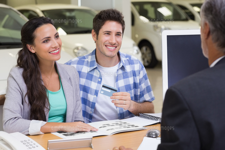 Smiling couple holding credit card to buy a carの写真素材 [FYI00005168]