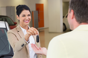 Smiling businesswoman giving car key to happy customerの写真素材 [FYI00005173]