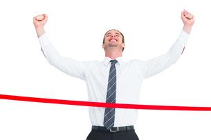 Happy businessman crossing the finish lineの素材 [FYI00005184]