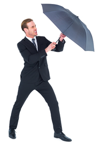 Businessman holding umbrella to protect himselfの写真素材 [FYI00005187]