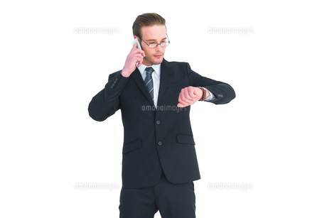 Serious businessman phoning while checking timeの素材 [FYI00005190]