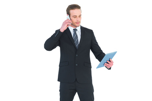 Serious businessman on the phone holding tabletの写真素材 [FYI00005191]