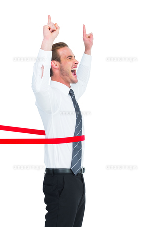 Happy businessman crossing the finish line and pointing upの素材 [FYI00005192]