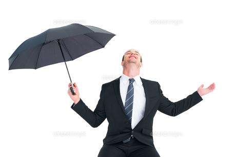Businessman sheltering under black umbrella testingの写真素材 [FYI00005194]