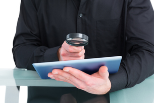 Businessman looking at tablet with magnifying glassの写真素材 [FYI00005196]