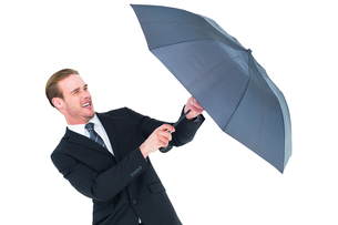 Businessman holding umbrella to protect himselfの写真素材 [FYI00005198]