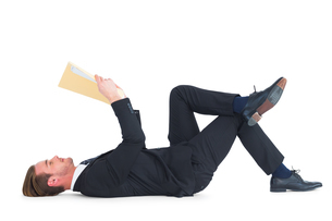 Relaxed businessman lying and reading documentの写真素材 [FYI00005200]