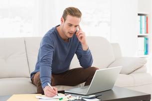 Serious man paying his bills on laptopの写真素材 [FYI00005201]