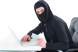 Hacker using laptop and credit cardの写真素材 [FYI00005204]