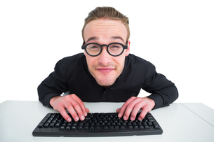 Smiling businessman typing on keyboard at deskの写真素材 [FYI00005215]