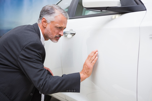 Focused businessman looking at the car bodyの写真素材 [FYI00005217]