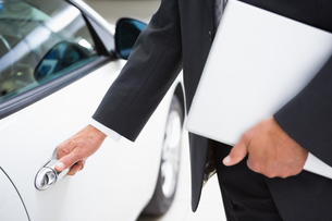 Man holding a car door handles while holding clipboardの素材 [FYI00005220]