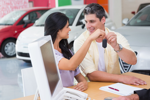 Smiling couple holding their new car keyの写真素材 [FYI00005224]