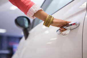 Woman holding a car door handlesの素材 [FYI00005232]