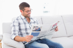 Relaxing man on a sofa with a newspaperの写真素材 [FYI00005236]