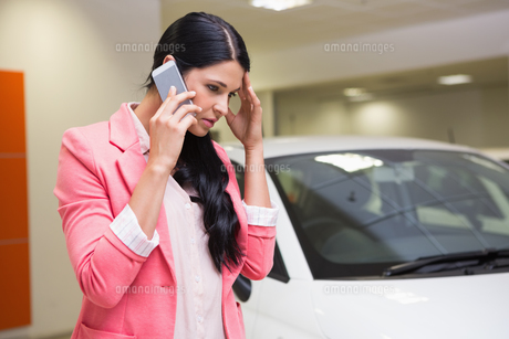 Sad woman calling someone with her mobile phoneの写真素材 [FYI00005238]