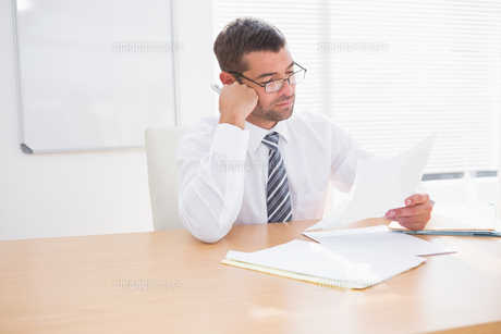 Focused businessman reading documentの写真素材 [FYI00005242]