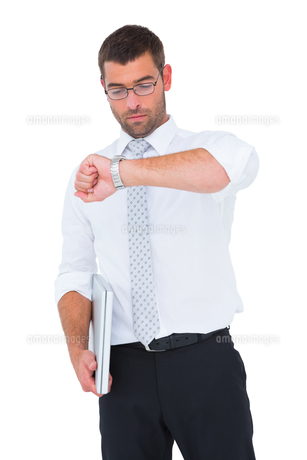 Serious businessman holding laptop checking timeの素材 [FYI00005252]