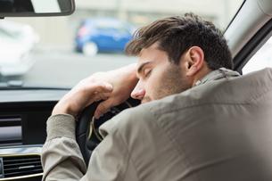 Drunk man slumped on steering wheelの写真素材 [FYI00005265]