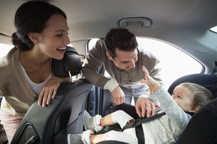 Parents securing baby in the car seatの写真素材 [FYI00005282]