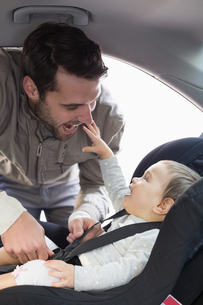 Father securing baby in the car seatの写真素材 [FYI00005288]