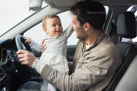 Father playing with baby in drivers seatの写真素材 [FYI00005294]