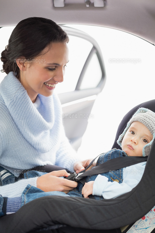 Mother securing her baby in the car seatの写真素材 [FYI00005296]