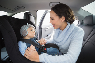 Mother securing her baby in the car seatの写真素材 [FYI00005300]