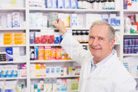 Smiling pharmacist taking medicine from shelfの写真素材 [FYI00005345]