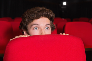 Young man watching a scary filmの素材 [FYI00005352]