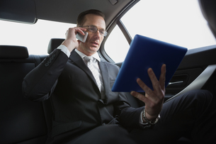 Businessman on the phone holding tablet pcの写真素材 [FYI00005406]