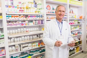 Smiling senior pharmacist writing on clipboardの写真素材 [FYI00005407]